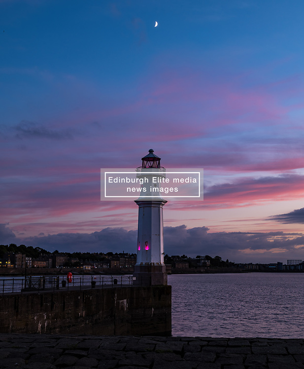 Edinburgh, Scotland, UK, 16th June 2021. Sunset at Newhaven Harbour: A crescent moon sets over the harbour just after sunset with the lighthouse lit up at dusk.<br /> Sally Anderson   EdinburghElitemedia.co.uk