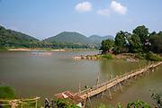 Image of a bamboo bridge crossing the Nam Khan River near its mouth, entering the Mekong River, Luang Prabang, Laos.