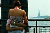 EEUU. Nueva York.<br /> Pareja abrazándose en Battery Park con la estatua de la Libertad al fondo.<br /> <br /> © JOAN COSTA