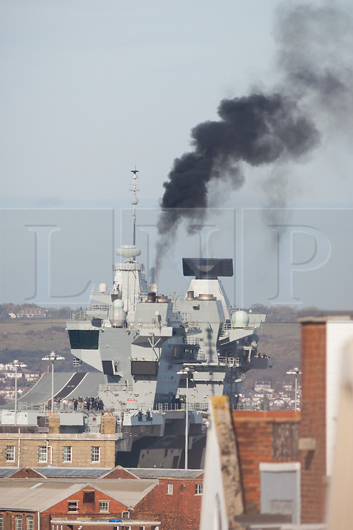© Licensed to London News Pictures. 30/10/2017. Portsmouth, UK.  Black smoke billows from the funnels of the Royal Navy's flagship, HMS Queen Elizabeth, as she prepares to depart Her Majesty's Naval Base (HMNB) Portsmouth for the first time since her arrival on 16/08/2017.  The new aircraft carrier is heading back to sea for the second stages of her sea trials.<br /> <br /> Flight trials involving the new F-35B Joint Strike Fighter are expected to take place off the coast of the U.S. next year, and she is due to come into service in the early 2020s.  Photo credit: Rob Arnold/LNP