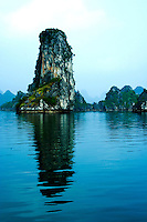 Karst Reflection at Halong Bay - a UNESCO World Heritage site - the bay features thousands of limestone karst isles in various sizes and shapes. Legend has it that long ago when the Vietnamese were fighting Chinese invaders the gods sent a family of dragons to help defend the land. These dragons began spitting out jewels and jade. These jewels turned into the islets dotting the bay linking together to form a great wall against the invaders. The people kept their land safe and formed what later became the country of Vietnam. After that, dragons were interested in peaceful sightseeing of the Earth and decided to live here.