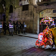Prince Jamal works as a live tourist attraction at and around Las Ramblas. In the picture, Jamal and his eccentric and noisy moped are trapped between riot police and a squatter's demonstration.