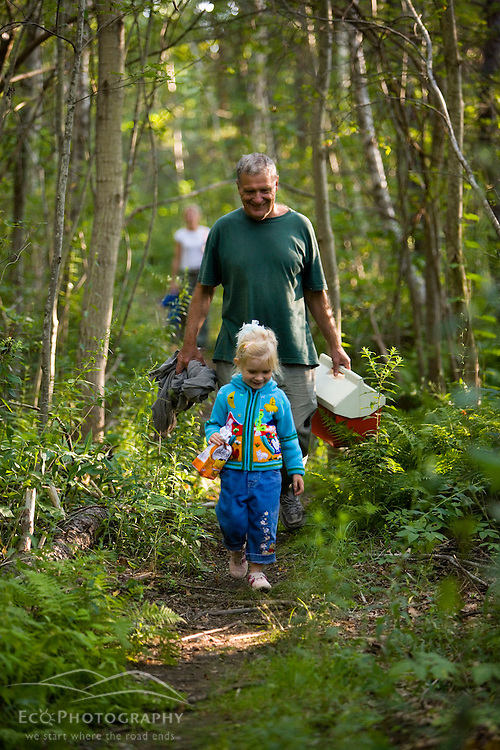 A man walks with his young granddaughter on a trail in the woods in Gloucester, Massachusetts.  Goose Cove preserve, Essex County Greenbelt Association.