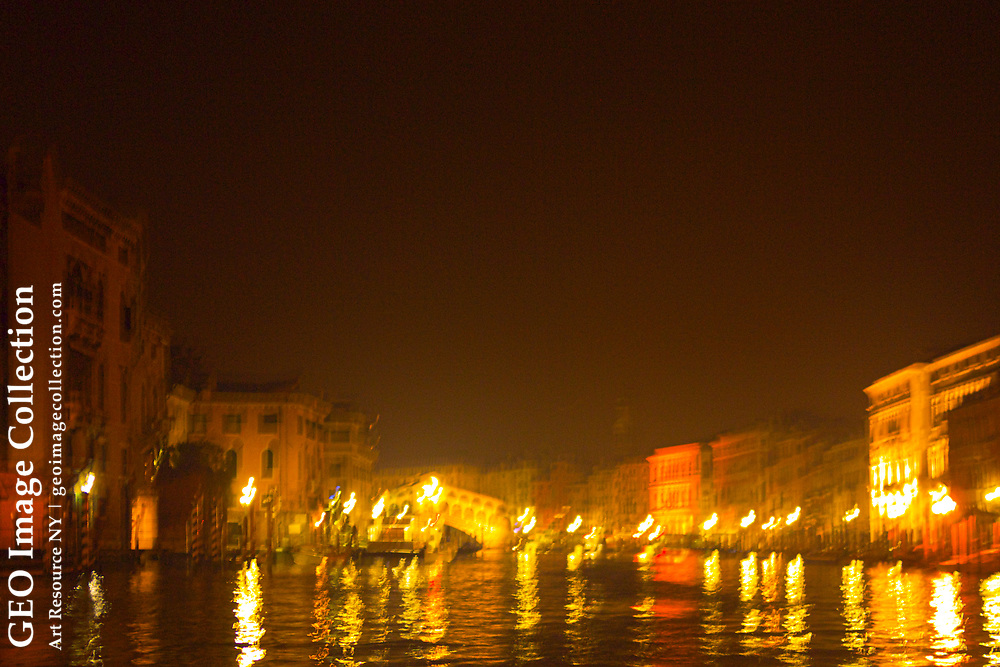 The Ponte Rialto and reflections in the canal at night.