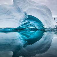 'Blue Arch' – Arrowsmith Peninsula, South of Antarctic Circle<br /> Calm waters result in an almost perfect reflection from this      iceberg. As ice get buried further in the glacier, it gets         compressed and drives out air bubbles. Without the scattering    effect of air bubbles, light can penetrate ice more deeply.  To           the human eye, ancient glacial ice acts like a filter, absorbing            red and yellow light and reflecting blue light, creating the        beautiful blue hues of the iceberg.