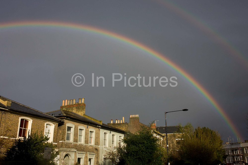 Double rainbows arc over houses in Brixton. After a rain shower over this area of south London and with skies still dark from the passing squall, we look up at the sky and the arcing rainbow that curves over the rooftops of period homes. Sunlight shines on their walls and windows and the colours of the spectrum - natural phenomena - is a feature of meteorology seen as a sign of good fortune, the symbol for an omen for luck and an auspicious future.