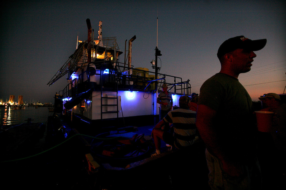 Tugboat crews relax at night on a dock in Sabine Pass Saturday September 20, 2008.  Many crews had been called in to help move rigs and boats that were scattered by Hurricane Ike.