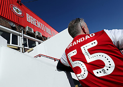 A Brentford fan rests against a stairway outside the stadium before the Sky Bet Championship match at Griffin Park, London.