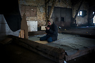 A migrant is seen praying in a makeshift mosque in one of the warehouses used as shelter by migrants in Belgrade train station. Belgrade, Serbia. March 20th, 2017. Federico Scoppa