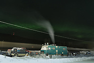 The Alaska Railroad passes by an RV being used as a residence while the Aurora Borealis shines overhead