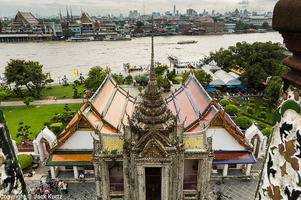 """23 SEPTEMBER 2013 - BANGKOK, THAILAND:     The main entrance to Wat Arun with the Chao Phraya River and city of Bangkok in the background. The full name of the temple is Wat Arunratchawararam Ratchaworamahavihara. The outstanding feature of Wat Arun is its central prang (Khmer-style tower). The world-famous stupa, known locally as Phra Prang Wat Arun, will be closed for three years to undergo repairs and renovation along with other structures in the temple compound. This will be the biggest repair and renovation work on the stupa in the last 14 years. In the past, even while large-scale work was being done, the stupa used to remain open to tourists. It may be named """"Temple of the Dawn"""" because the first light of morning reflects off the surface of the temple with a pearly iridescence. The height is reported by different sources as between 66,80 meters and 86 meters. The corners are marked by 4 smaller satellite prangs. The temple was built in the days of Thailand's ancient capital of Ayutthaya and originally known as Wat Makok (The Olive Temple). King Rama IV gave the temple the present name Wat Arunratchawararam. Wat Arun officially ordained its first westerner, an American, in 2005. The central prang symbolizes Mount Meru of the Indian cosmology. The temple's distinctive silhouette is the logo of the Tourism Authority of Thailand.       PHOTO BY JACK KURTZ"""