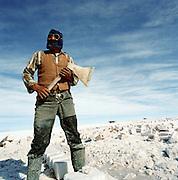 Portrait of Miner holding axe on Salar de Uyuni salt flats, Potosi, Bolivia. The Salar de Uyuni are the worlds largest salt flats.
