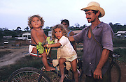 CAMPESINO FAMILY Amazon, near Boavista, northern Brazil, South America. Poor campesino family returning home,a father his wife with their two daughters on a bicycle. Ecological biosphere and fragile ecosystem where flora and fauna, and native lifestyles are threatened by progress and development. The rainforest is home to many plants and animals who are endangered or facing extinction. This region is home to indigenous primitive and tribal peoples including the Yanomami and Macuxi.