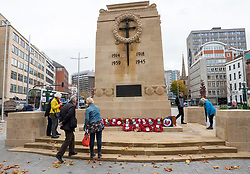 © Licensed to London News Pictures; 11/11/2020; Bristol, UK. People look at the wreaths on display on Remembrance Day at the Bristol Cenotaph in the city centre. The normal large military parade and civic procession was cancelled due to the national lockdown restrictions for the Covid-19 coronavirus pandemic, but around 40 people gathered for the two-minute silence that traditionally takes place at 11.00am, recognising the precise time that the hostilities ceased in 1918 – the 11th hour of the 11th day of the 11th month. Photo credit: Simon Chapman/LNP.