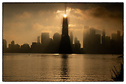 The sun hangs above the World Trade Center in Lower Manhattan like Sauron's eye over Middle Earth.