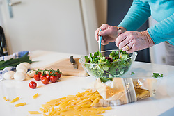 Old woman mixing salad on the kitchen table