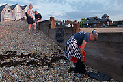 As the sun sets over fading daylight and calm waters of the Thames Estuary, a wild sea swimmer changes into his costume before his regular evening dip, on 18th July 2020, in Whitstable, Kent, England.