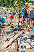 The Stone Circle is crowded with revellers from the night before - most rest but some are still up for dancing or chat. The 2015 Glastonbury Festival, Worthy Farm, Glastonbury.