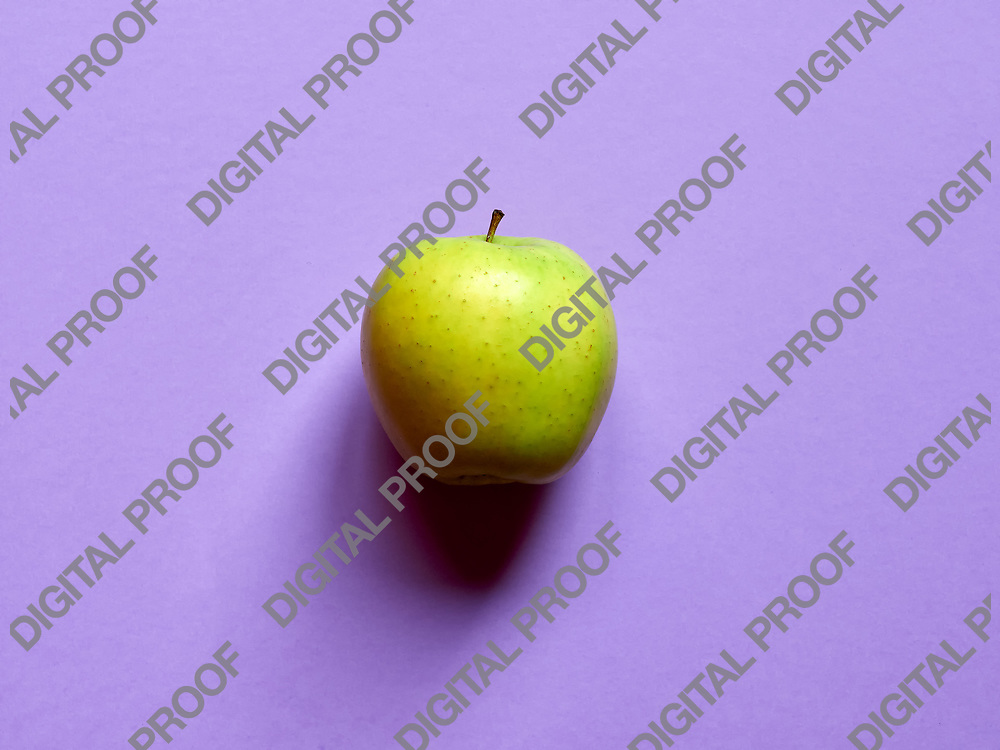 Above view of a Green apple isolated in a violet background in studio