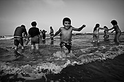 """A child runs in the sea during """"holy bath"""" ritual the St. Bartolomeu celebration. The """"holy bath"""" is believed to drive away evil and cure diseases related with """"demonic possession"""", such as stuttering or epilepsy. This tradition that dates back to the sixteenth century (1566), and it claims the devil is on the loose during this day. Every year on 24 August  faith and tradition join thousands of people at the feast of St. Bartolomeu do Mar, for ritual that mixes the sacred and the profane."""