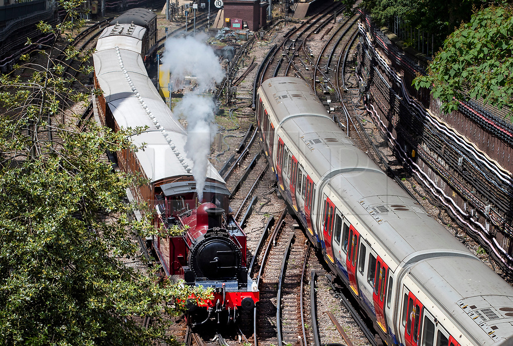 © Licensed to London News Pictures. 22/06/2019. London, UK. A Metropolitan Locomotive No 1 steam engine passes a modern electric tube train (R) as it pulls a set of vintage coaches out of High Street Kensington Undergound station to celebrate the 150th anniversary of the district line. London Transport Museum is running steam services, with vintage coaches, between Ealing Broadway and High Street Kensington over this weekend. Photo credit: Peter Macdiarmid/LNP