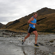 Runner James Somerville crosses Moke Creek on the Ben Lomond High Country Station during the Pure South Shotover Moonlight Mountain Marathon and trail runs. Moke Lake, Queenstown, New Zealand. 4th February 2012. Photo Tim Clayton