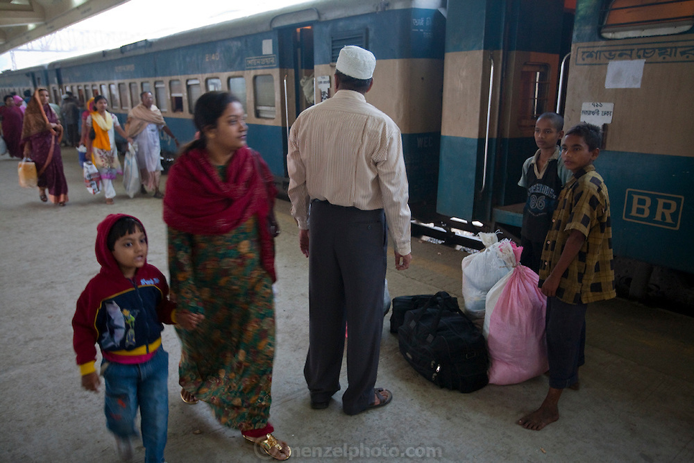 A traveller hires Alamin Hasan (right) to carry his luggage at the Kamalapur Railway Station in Dhaka, Bangladesh, where he works as a porter.  (Alamin Hasan is featured in the book What I Eat: Around the World in 80 Diets.) MODEL RELEASED.