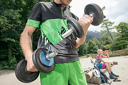 Young man lifting dumbbells while woman is drinking water in the background, Kampenwand, Bavaria, Germany