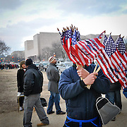 A street vendor hides his face behind Obama themed flags. Vendors of all types saturated the National Mall hoping to make a quick buck on the day prior to the historic inauguration.
