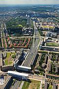 Nederland, Noord-Holland, Amsterdam, 14-06-2012; Ring A10 - West, links Bos en Lommer, rechts Slotervaart met Kolenkitbuurt en kerk De Kolenkit (Opstandingskerk). Ring A10 en Poortgebouw met daarnaast aan de snelweg voormalig GAK-gebouw...De wijk is onderdeel van de Westelijke Tuinsteden, gerealiseerd op basis van het Algemeen Uitbreidingsplan voor Amsterdam (AUP, 1935). Voorbeeld van het Nieuwe Bouwen, open bebouwing in stroken, langwerpige bouwblokken afgewisseld met groenstroken. ..Overview residential district Slotervaart, one of the western garden cities of Amsterdam-west and the skyline in southern direction.  Constructed on the basis of the General Extension Plan for Amsterdam (AUP, 1935). Example of the New Building (het Nieuwe Bouwen), detached in strips, oblong housing blocks alternated with green areas, built in fifties and sixties of the 20th century. The church is nicknamed Kolenkit (coal-hod) and so this district is called the Coal-hod district. A10 Ringroad crosses the neighbourhood. .luchtfoto (toeslag), aerial photo (additional fee required).foto/photo Siebe Swart