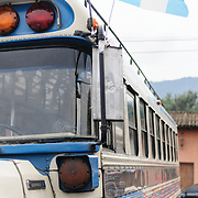 A blue and white with Guatemalan flag chicken bus behind the Mercado Municipal (town market) in Antigua, Guatemala. From this extensive central bus interchange the routes radiate out across Guatemala. Often brightly painted, the chicken buses are retrofitted American school buses and provide a cheap mode of transport throughout the country.
