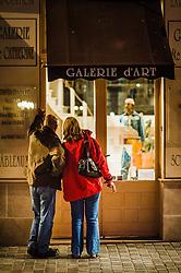 A couple look in an art gallery window in Honfleur, France