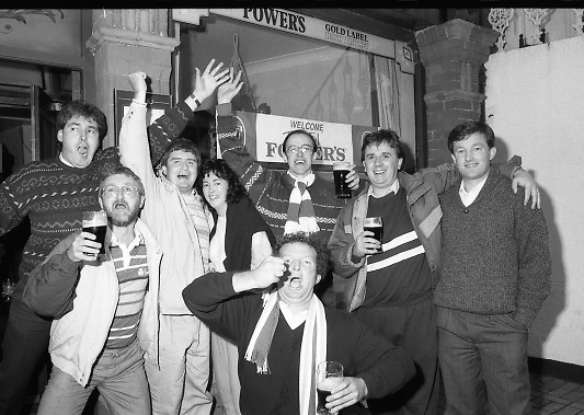Republic Fans Celebrate Win.  (T8)..1989..11.10.1989..10.11.1989..11th October 1989..As part of the Italia 90 campaign,The Republic of Ireland took on Northern Ireland in a qualifier. A 3 nil win over Northern ireland virtually guaranteed the Republic a spot in the World Cup Finals..Rep. Ireland: Packie Bonner (Glasgow Celtic), Chris Morris (Glasgow Celtic), Mick McCarthy (Olympique Lyon) capt, Kevin Moran (Sporting Gijon), Steve Staunton (Liverpool), Ray Houghton (Liverpool), Ronnie Whelan (Liverpool), Andy Townsend (Norwich City), Kevin Sheedy (Everton), John Aldridge (Real Sociedad), Tony Cascarino (Millwall).Subs: David O'Leary (Arsenal) for Staunton 77 mins..N. Ireland: Dunlop, Fleming, McDonald, Donaghy, Worthington, D Wilson, McCreery, Whiteside, M O'Neill, Clarke, Dennison.Subs: C O'Neill for McCreery 71 mins, K Wilson for M O'Neill 79 mins.Goal scorers; Whelan,Cascarino,Houghton....Republic supporters from Cork are pictured celebrating the win in the '51Bar' (a Dublin pub) included are;Billy Barry, John McCarthy, Harry McCarthy, Catherine McCarthy, Declan Farmer and Michael O'Leary.