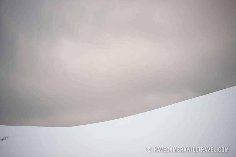 Gentle slopes of snow and ice stand out against gray skies along the Lemaire Channel in Antarctica.