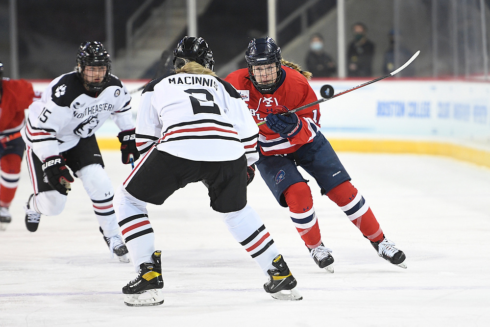 ERIE, PA - MARCH 15: Leah Marino #12 of the Robert Morris Colonials dumps the puck as Lauren MacInnis #2 of the Northeastern Huskies defends in the first period during the NCAA Tournament Quarterfinals game at the Erie Insurance Arena on March 15, 2021 in Erie, Pennsylvania. (Photo by Justin Berl/Robert Morris Athletics)