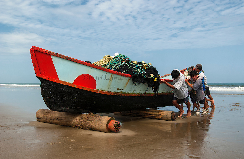 Fishing boat being hauled up onto the beach<br /> San Pablo<br /> Guayas Province<br /> South coast of ECUADOR.  South America