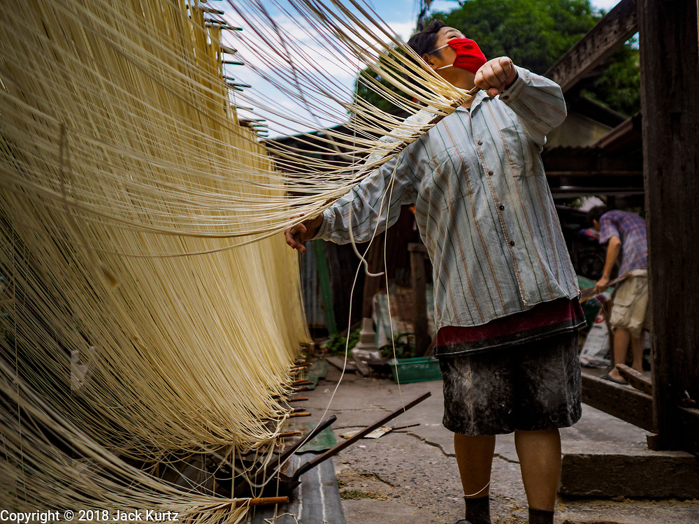 """29 DECEMBER 2018 - BANGKOK, THAILAND: A woman checks for rain clouds while she stretches longevity noodles during the drying process in front of her family shophouse. The noodles can't be left out if it rains. The family has been making traditional """"mee sua"""" noodles, also called """"longevity noodles"""" for three generations in their home in central Bangkok. They use a recipe brought to Thailand from China. Longevity noodles are thought to contribute to a long and healthy life and  are served on special occasions, especially Chinese New Year, which is February 4, 2019. These noodles were being made for Chinese New Year.      PHOTO BY JACK KURTZ"""