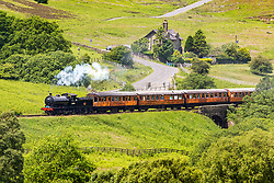 © Licensed to London News Pictures. 18/06/2018. Goathland UK. 1923 Locomotive 65894 travels through the village of Goathland today in the North Yorkshire Moors on route to Pickering. Photo credit: Andrew McCaren/LNP