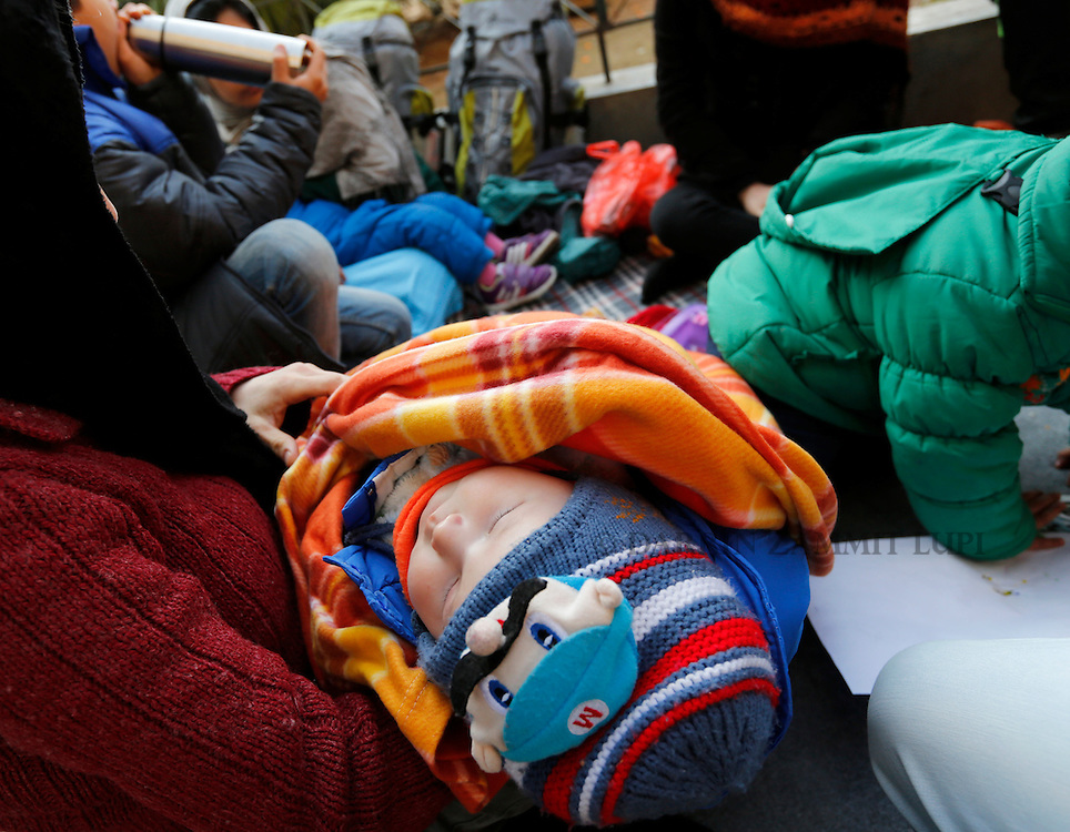A migrant baby sleeps in a woman's arms in Victoria Square in central Athens, Greece, January 27, 2016. <br /> Photo: Darrin Zammit Lupi