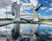The Kelpies, built of structural steel in 2013, are the world's largest pair of equine sculptures. Towering 30 meters above the Forth & Clyde Canal, these two horse head artworks are a monumental tribute to the horse power heritage (pulling wagons, ploughs, barges and coalships) vital to early industrial Scotland. Scottish sculptor Andy Scott designed these twin 300-tonne feats of engineering. Visit the Kelpies in the Helix parkland project, Falkirk, Scotland, United Kingdom, Europe. This image was stitched from several overlapping photos.