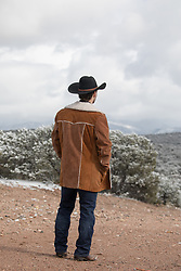 cowboy looking out on snow covered mountains