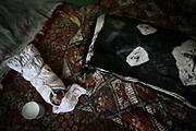 Qamar, at right,  a 26-year-old tuberculosis patient who died of postpartum complications two weeks after the delivery, and her baby lie in their house in the village in Shohada district in Badakshan province, Afghanistan, Monday, May 21, 2007.