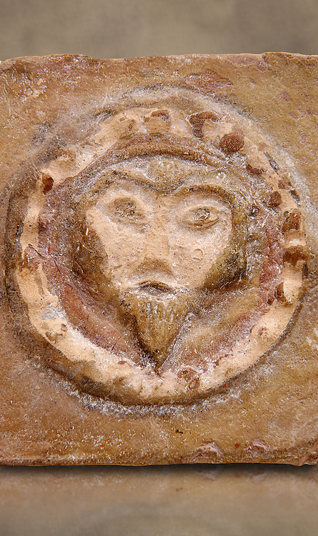Detail of a 6th-7th Century Eastern Roman Byzantine  Christian Terracotta tiles depicting Christ - Produced in Byzacena -  present day Tunisia. <br /> <br /> These early Christian terracotta tiles were mass produced thanks to moulds. Their quadrangular, square or rectangular shape as well as the standardised sizes in use in the different regions were determined by their architectonic function and were designed to facilitate their assembly according to various combinations to decorate large flat surfaces of walls or ceilings. <br /> <br /> Byzacena stood out for its use of biblical and hagiographic themes and a richer variety of animals, birds and roses. Some deer and lions were obviously inspired from Zeugitana prototypes attesting to the pre-existence of this province's production with respect to that of Byzacena. The rules governing this art are similar to those that applied to late Roman and Christian art with, in the case of Byzacena, an obvious popular connotation. Its distinguishing features are flatness, a predilection for symmetrical compositions, frontal and lateral representations, the absence of tridimensional attitudes and the naivety of some details (large eyes, pointed chins). Mass production enabled this type of decoration to be widely used at little cost and it played a role as ideograms and for teaching catechism through pictures. Painting, now often faded, enhanced motifs in relief or enriched them with additional details to break their repetitive monotony.<br /> <br /> The Bardo National Museum Tunis, Tunisia