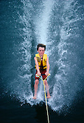 Micheal McCormick, age 7 kicks off his skis when he moving about 15 m.p.h. 24 kmh.  to barefoot ski in Cypress Gardens, Florida 1982