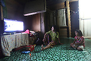 August 2012: Penan natives watch a panoramic television screen, powered by a petrol driven generator, at the headman's house. Long Adang, Limbang district, Sarawak, Borneo<br /> <br /> Penan indigenous native people, nomadic decades ago, have been forced to move up-river, to settled accomodation, far from their original hunter-gatherer grounds. The sound of chainsaws is not too distant, oil palm plantations are looming and the pipeline is right next door. Long Adang and Long Gita, Limbang Sarawak, Borneo..The huge Petronas Sabah-Sarawak pipeline is being built across the Borneo rainforest through native areas. Petronas is the government cash cow which funds about 45% of its budget. New roads are being built, though much of the transport follows the existing roads and infrastructure created by logging. Whilst the government heralds the project as a source of jobs for local people, it is unlikely to bring much but wanton damage to rainforest habitat and paving the way for further deforestation by oil palm plantations. Sarawak's primary rainforests have been systematically logged over decades, threatening the sustainable lifestyle of its indigenous peoples who relied on nomadic hunter-gathering and rotational slash & burn cultivation of small areas of forest to survive. Now only a few areas of pristine rainforest remain; for the Dayaks and Penan this spells disaster, a rapidly disappearing way of life, forced re-settlement, many becoming wage-slaves. Large and medium size tree trunks have been sawn down and dragged out by bulldozers, leaving destruction in their midst, and for the most part a primary rainforest ecosystem beyond repair. Nowadays palm oil plantations and hydro-electric dam projects cover hundreds of thousands of hectares of what was the world's oldest rainforest ecosystem which had some of the highest rates of flora and fauna endemism, species found there and nowhere else on Earth