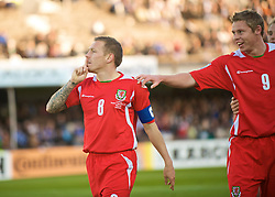 HELSINKI, FINLAND - Saturday, October 10, 2009: Wales' captain Craig Bellamy silences the Finland fans, who chanted homophobic songs at him, as he celebrates scoring the equalising goal against Finland during the 2010 FIFA World Cup Qualifying Group 4 match at the Olympic Stadium. (Pic by David Rawcliffe/Propaganda)
