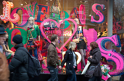 © licensed to London News Pictures. London, UK 13/02/2012. Shoppers walking past a shop on the day before Valentine's Day in Oxford Street, London. Photo credit: Tolga Akmen/LNP