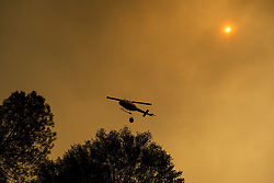 July 18, 2017 - Mariposa County, California, U.S. - The sun shines though smoke from the Detwiler fire as a helicopter carries water douse flames along Highway 49 in Mariposa County. (Credit Image: © Andrew Kuhn/The Merced Sun Star via ZUMA)