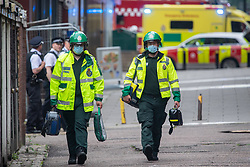 """© Licensed to London News Pictures. 28/06/2021. London, UK. London Ambulance Service (LAS) paramedics inside a cordon. One hundred firefighters tackled a fire near Elephant and Castle railway station in southeast London. London Fire Brigade (LFB) said three commercial units in railway arches were """"completely alight"""", in addition to six cars and a telephone box. Photo credit: Peter Manning/LNP"""