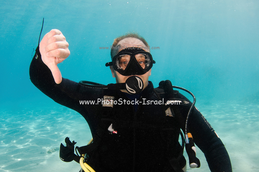 Underwater Hand signs scuba diver demonstrates the sign language for divers. Descend, or I am going down: A fist is made with one hand, thumb extended downward, and hand is moved downward to emphasize direction of travel.